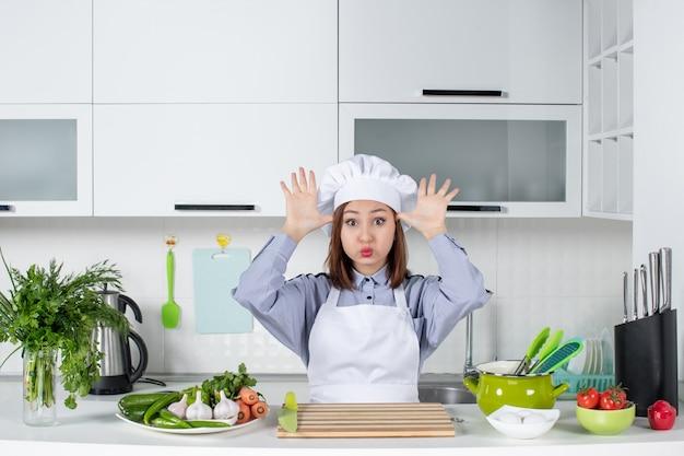 Vooraanzicht van verwarde en emotionele vrouwelijke chef-kok en verse groenten poseren voor de camera in de witte keuken