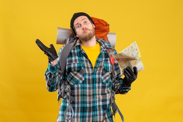 Vooraanzicht van verwarde jonge backpacker met zwarte hoed met reiskaart