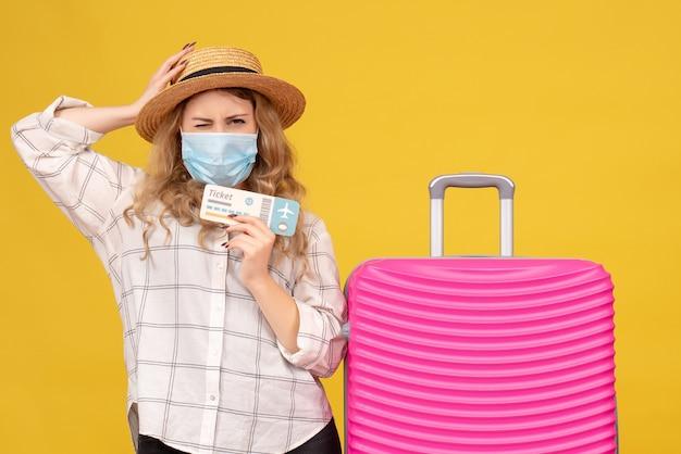 Vooraanzicht van verwarde jonge dame die masker draagt dat kaartje toont en dichtbij haar roze zak op geel staat