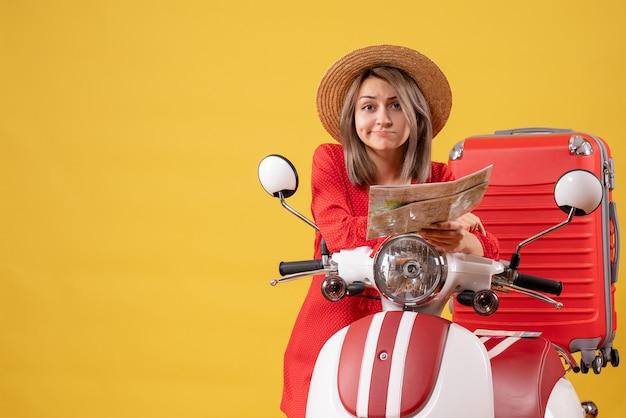 Vooraanzicht van verwarde jonge dame in rode jurk met kaart in de buurt van bromfiets