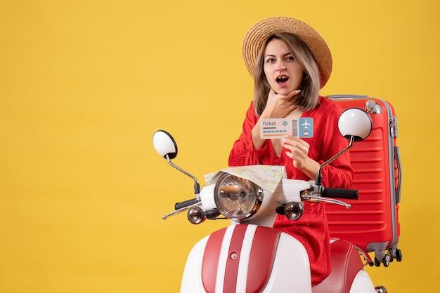 Vooraanzicht van verwarde jonge dame in rode jurk met kaartje hand op haar kin op bromfiets te zetten