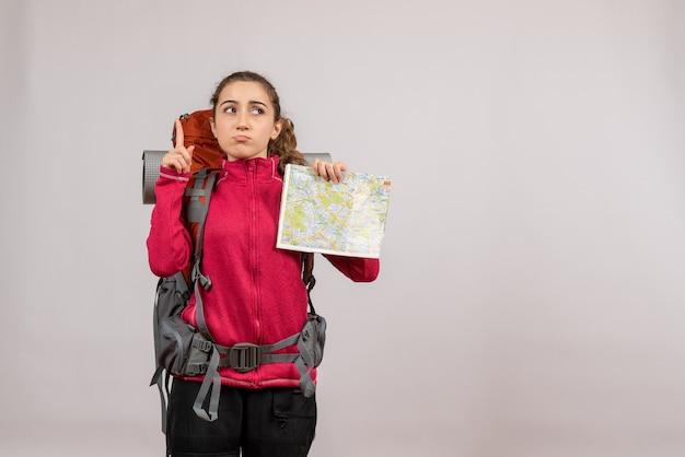 Vooraanzicht van verwarde jonge reiziger met grote rugzak met kaart wijzend op plafond op grijze muur