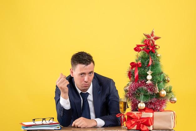 Vooraanzicht van verwarde man zit aan de tafel in de buurt van kerstboom en geschenken op geel