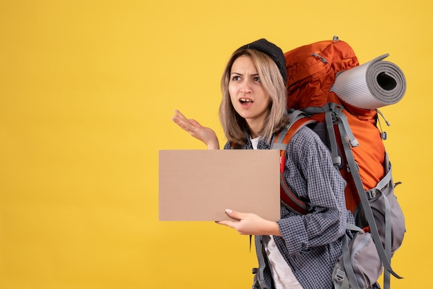 Vooraanzicht van verwarde reizigersvrouw met het karton van de rugzakholding