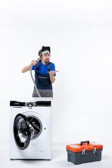 Vooraanzicht van verwarde reparateur in uniform staande achter wasmachine die afvoerpijp op witte muur uitblaast