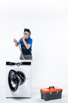 Vooraanzicht van verwarde reparateur in uniform staande achter wasmachine die pijp op witte muur blaast
