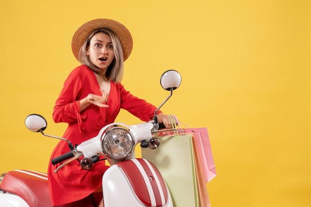 Vooraanzicht van verwarde vrouw in rode jurk op bromfiets met boodschappentassen