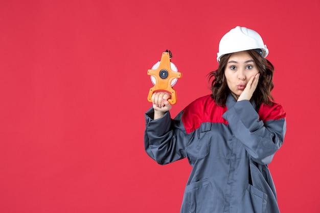 Vooraanzicht van verwarde vrouwelijke architect in uniform met bouwvakker met meetlint op geïsoleerde rode muur