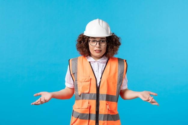 Vooraanzicht van verwarde vrouwelijke bouwer in uniform en helm op blauwe muur