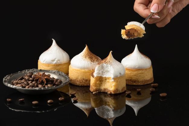 Vooraanzicht van vier desserts met cacao- en chocoladepoeder