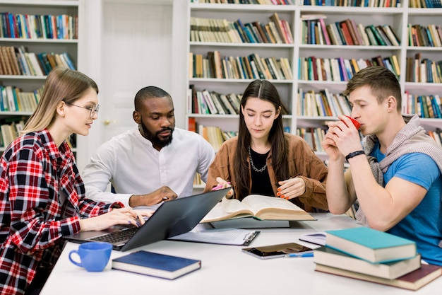 Vooraanzicht van vier knappe moderne slimme studenten van gemengd ras die in de leeszaal van de bibliotheek zitten en zich voorbereiden op examens of een wetenschappelijk project