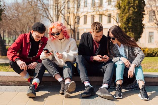 Vooraanzicht van vier vrienden die samen buiten hun smartphones controleren