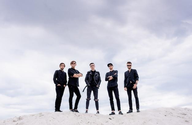 Vooraanzicht van vijf mannen die op de zandheuvel staan en naar de camera kijken