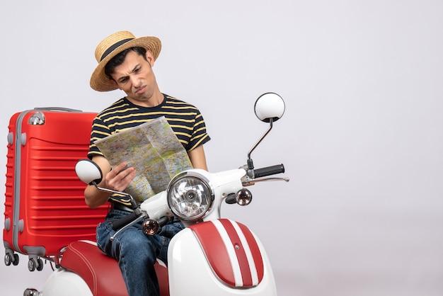Vooraanzicht van vreugdeloze jonge man met strooien hoed op bromfiets kijken naar locatie