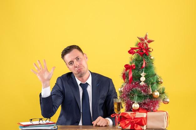 Vooraanzicht van vreugdeloze man die zijn hand opent aan de tafel in de buurt van kerstboom en geschenken op geel