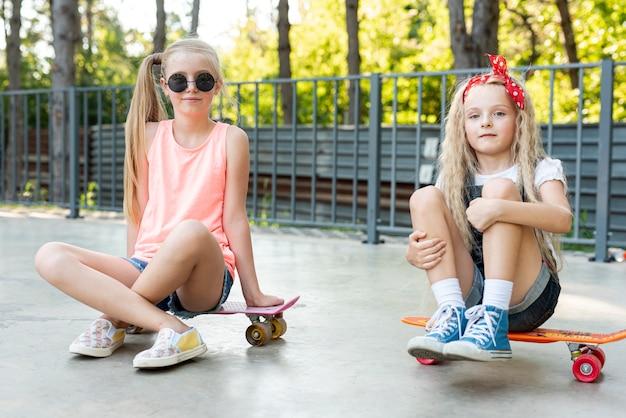 Vooraanzicht van vrienden die op skateboards zitten