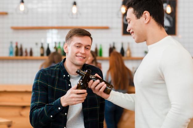 Vooraanzicht van vrienden juichen in café