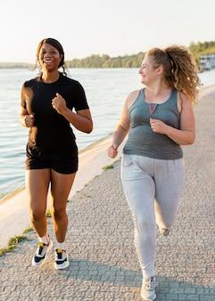 Vooraanzicht van vriendinnen joggen aan het meer
