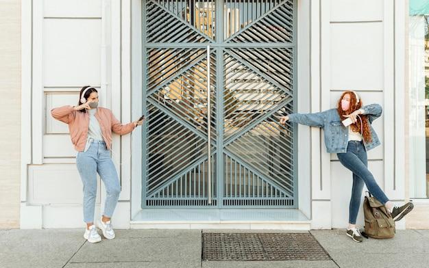 Vooraanzicht van vriendinnen met gezichtsmaskers buitenshuis met behulp van smartphones en dansen