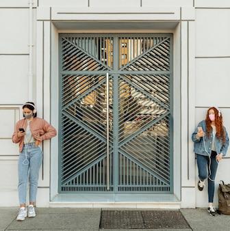 Vooraanzicht van vriendinnen met gezichtsmaskers buitenshuis met behulp van smartphones en koptelefoons