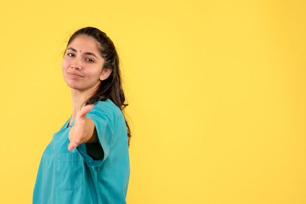 Vooraanzicht van vrij vrouwelijke arts die hand op gele muur geeft