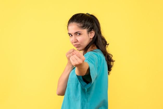 Vooraanzicht van vrij vrouwelijke arts die stoten op gele muur toont