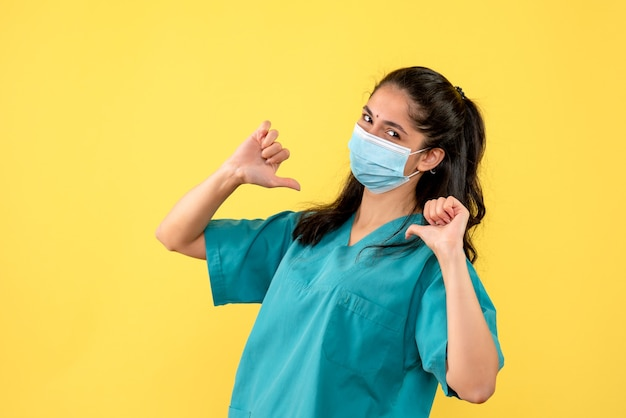 Vooraanzicht van vrij vrouwelijke arts met medisch masker die op zichzelf op gele muur richt