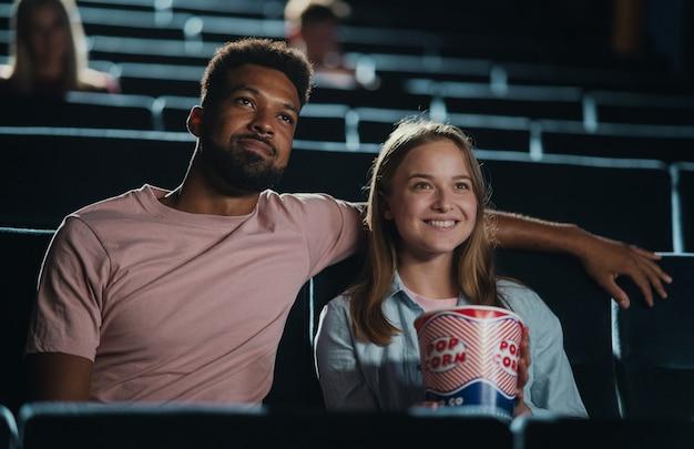 Vooraanzicht van vrolijk jong stel met popcorn in de bioscoop, film kijken.