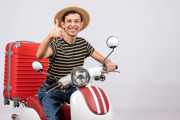 Vooraanzicht van vrolijke jonge man met strooien hoed op bromfiets duim opgevend