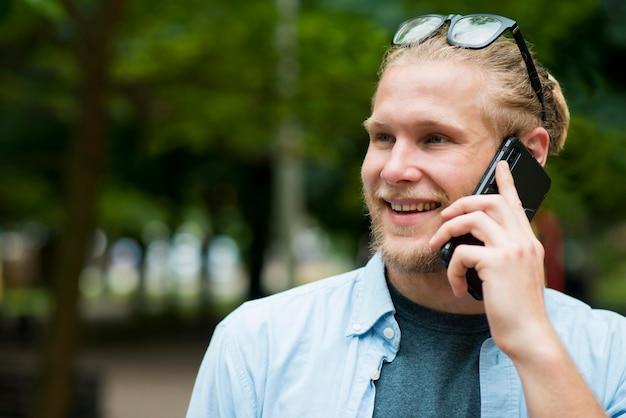 Vooraanzicht van vrolijke man praten over de telefoon