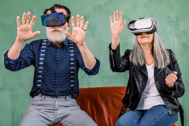 Vooraanzicht van vrolijke oudere man en vrouw, samen zittend op rode zachte stoel op groene achtergrond, en met behulp van vr bril headset, denkbeeldige scherm in de lucht aan te raken