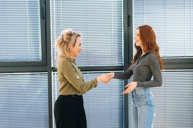 Vooraanzicht van vrolijke professionele vrouwelijke manager die de klant of klant een zakelijke deal geeft in de vergaderruimte van het kantoor bij het raam. jonge zakenvrouw groet collega voor de vergadering.
