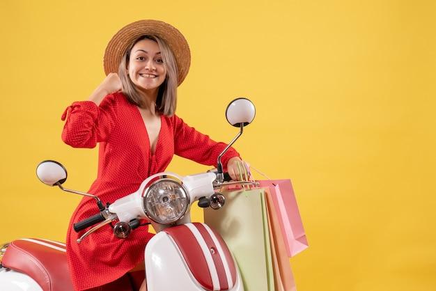Vooraanzicht van vrolijke vrouw in rode jurk op bromfiets met boodschappentassen