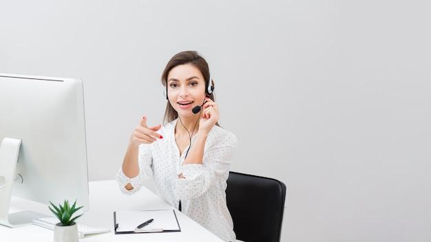 Vooraanzicht van vrouw bij bureau dat hoofdtelefoon en het richten draagt