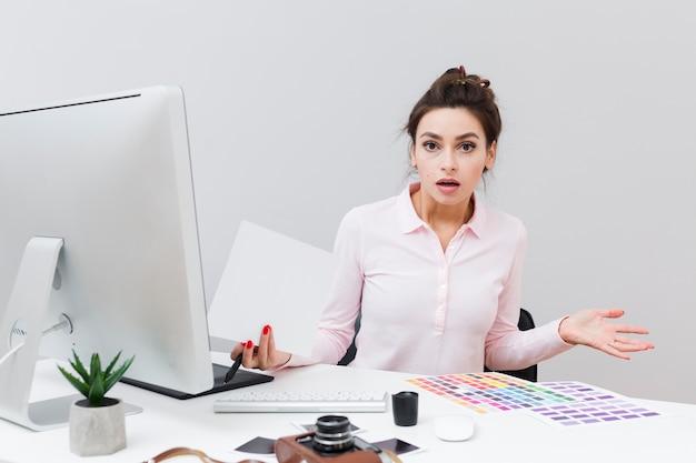 Vooraanzicht van vrouw bij bureau die geen idee heeft wat net gebeurde