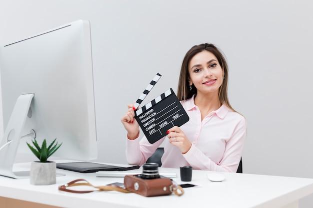 Vooraanzicht van vrouw bij bureau het stellen met een clapperboard