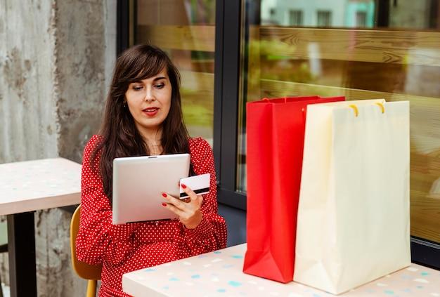 Vooraanzicht van vrouw die artikelen te koop bestellen met behulp van tablet