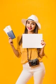 Vooraanzicht van vrouw die een camera draagt en vliegtickets en paspoort houdt