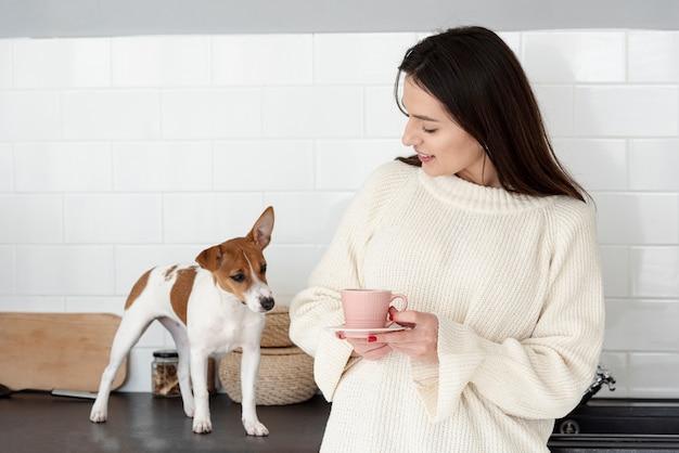 Vooraanzicht van vrouw die een mok en een hond houdt