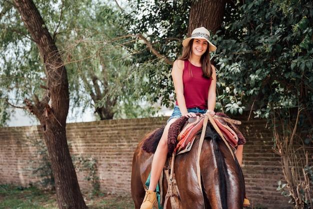 Vooraanzicht van vrouw die een paard berijdt