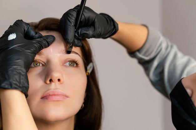 Vooraanzicht van vrouw die een wenkbrauwbehandeling krijgt van schoonheidsspecialiste