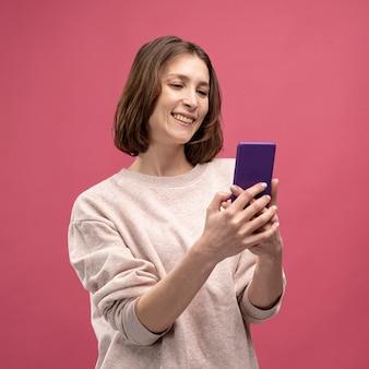 Vooraanzicht van vrouw die en smartphone glimlacht bekijkt