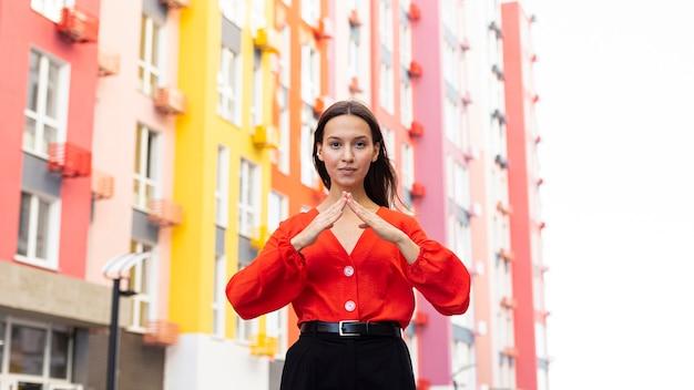 Vooraanzicht van vrouw die gebarentaal buitenshuis gebruikt