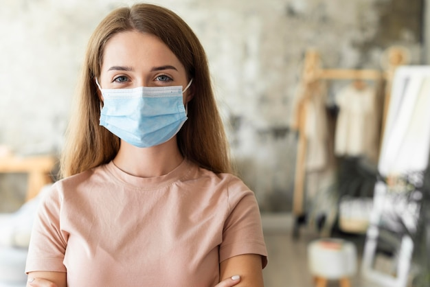 Vooraanzicht van vrouw die medisch masker met exemplaarruimte draagt