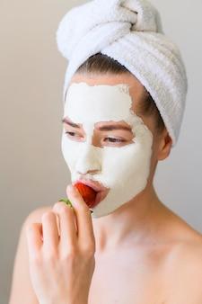 Vooraanzicht van vrouw die met gezichtsmasker aardbei eet