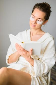 Vooraanzicht van vrouw die met oogflarden een boek leest