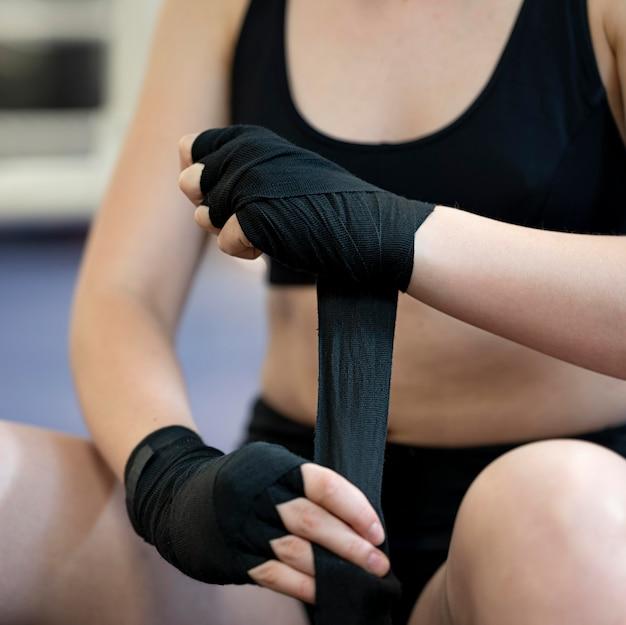Vooraanzicht van vrouw die op beschermende handschoenen zet