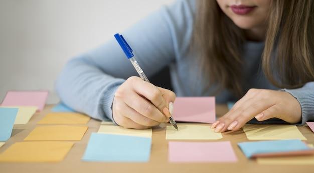 Vooraanzicht van vrouw die op kleverige nota's op het kantoor schrijven