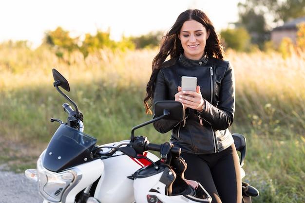 Vooraanzicht van vrouw die smartphone bekijkt terwijl ze tegen haar motorfiets leunt