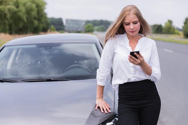 Vooraanzicht van vrouw die telefoon controleert